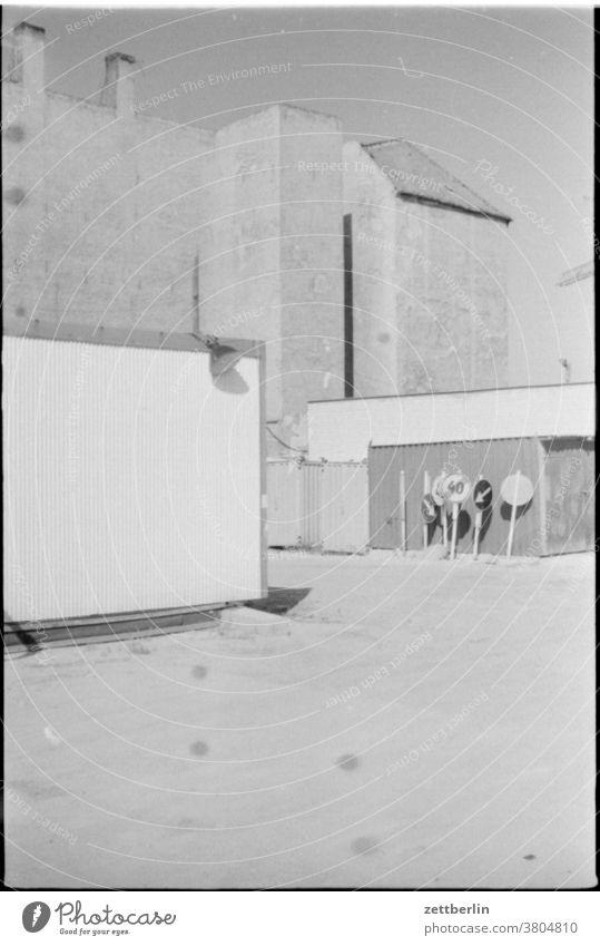 Verkehrsschilder vor leeren Fassaden haus baustelle brandmauer fassade trist traurig melancholie ddr ostberlin licht schatten unbelebt verkehrsschild platz