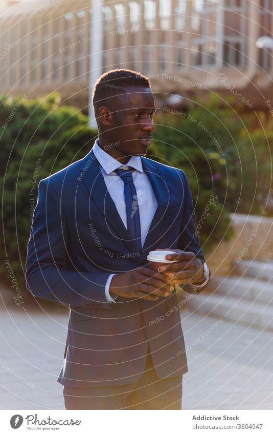 Eleganter schwarzer Geschäftsmann mit Kaffee zum Mitnehmen auf der Straße Imbissbude trinken urban formal modern Tasse Exekutive elegant Anzug Manager