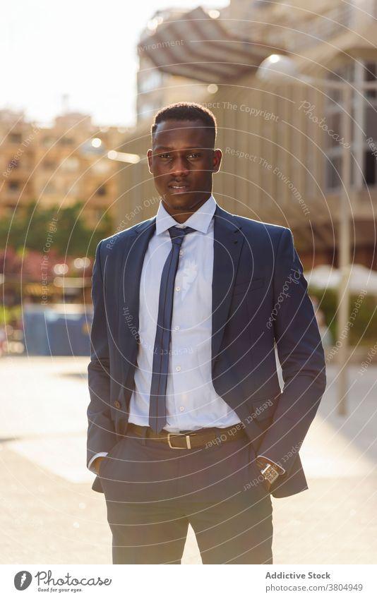 Schwarzer Geschäftsmann in formellem Anzug stehend in der Stadt selbstbewusst formal urban modern elegant Exekutive Erfolg Manager professionell Erwachsener