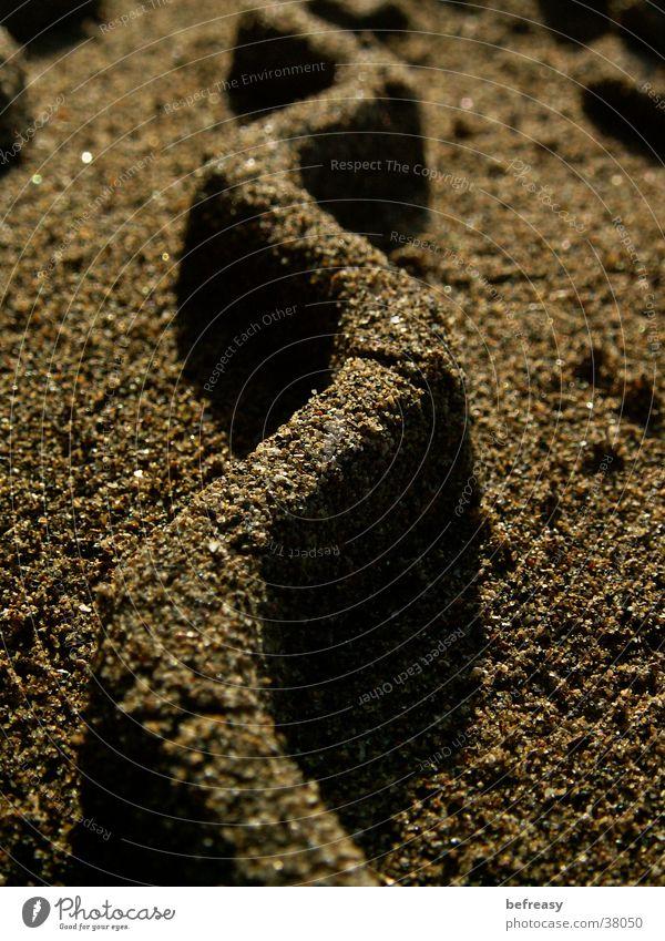 Sandwelle braun Wellen Zickzack Reifenspuren Sandkorn