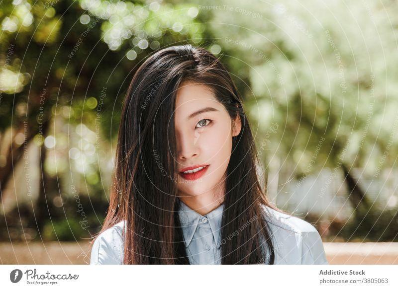 Verträumte junge ethnische Frau im Sommer Park traumhaft sich[Akk] entspannen Porträt Auge abdecken Stil feminin Vorschein Persönlichkeit Model asiatisch