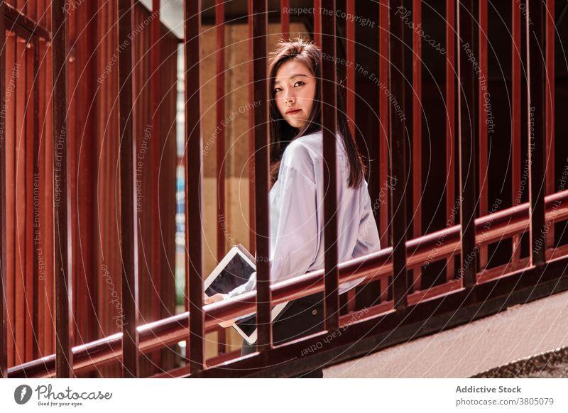 Selbstbewusste junge ethnische Frau geht unten auf der Straße Spaziergang im unteren Stockwerk selbstbewusst Hand-in-Tasche stilvoll Treppe Reling Großstadt