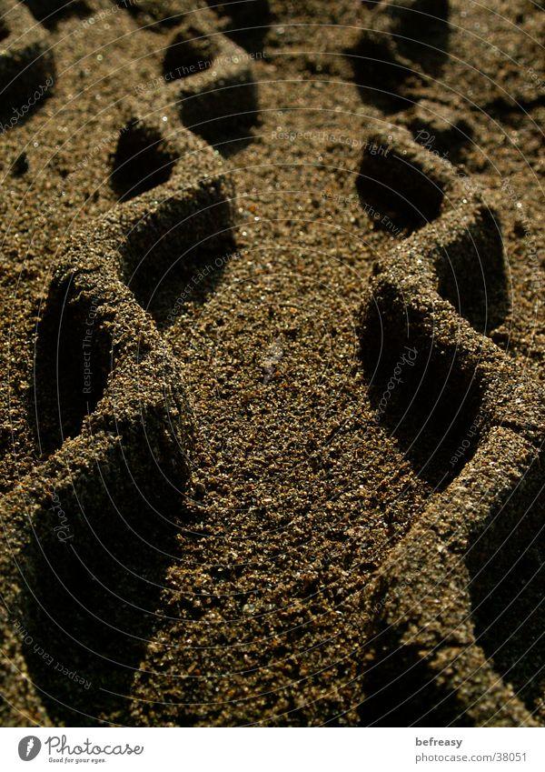 Sandwellen Strand Mauer braun Zickzack Reifenspuren