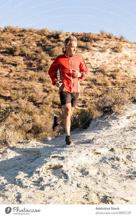 Sportler beim Joggen auf sandigem Untergrund in bergigem Gelände Mann laufen Halbwüste Hügel Training aktiv Jogger Gesundheit Natur Wohlbefinden Sand Übung
