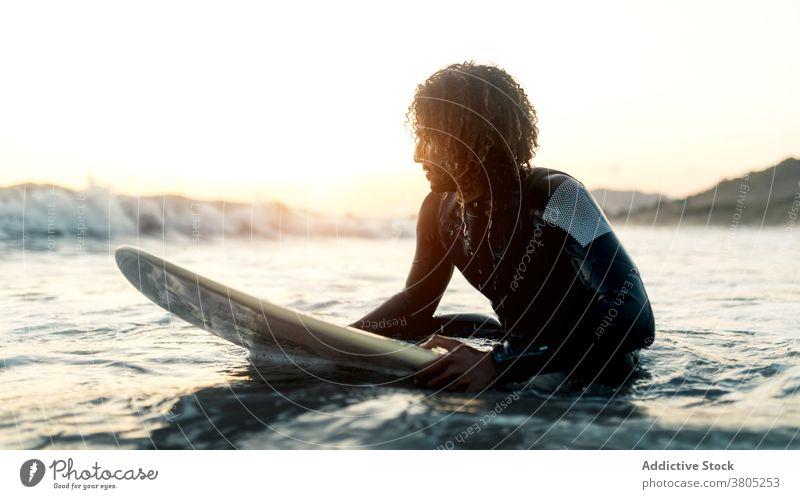 Konzentrierter Surfer schaut auf kommende Welle Mann winken MEER Meer Wassersport Sommer Fokus Freizeit Surfbrett männlich ernst besinnlich krause Haare