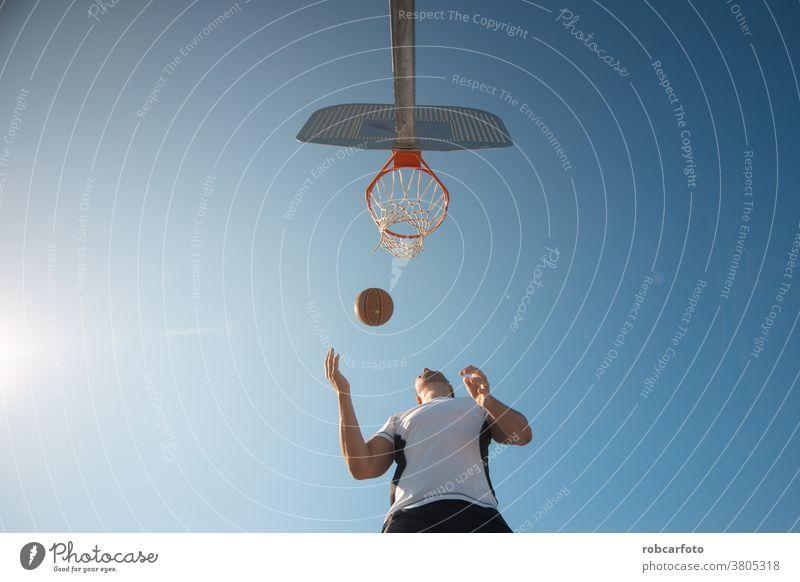 Mann, der auf der Straße auf einem Außenplatz Basketball spielt. Spaß Sport urban Menschen cool Männer Ball Schuss jung Spiel männlich Erwachsener Gericht