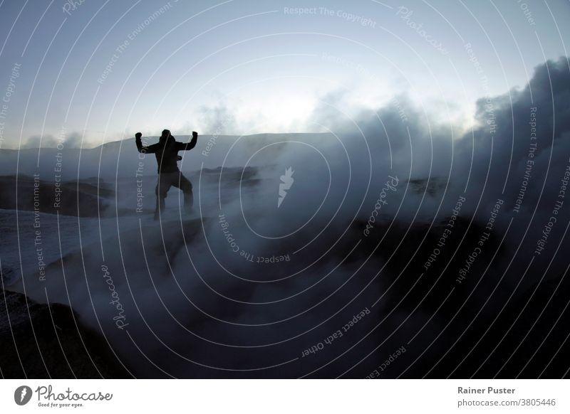 Silhouette eines Mannes inmitten von vulkanischem Rauch auf einem Vulkan in Salar de Uyuni, Bolivien, während des Sonnenaufgangs Errungenschaft Ziele erreichen