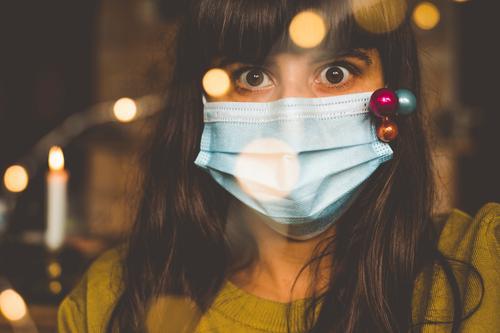 Eine Frau mit weihnachtlich dekorierter Maske blickt in die Kamera. Weihnachten während Corona. Einwegmaske Mundschutz ernst Blick in die Kamera Lichterkette