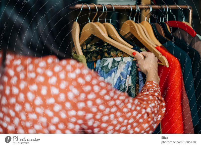 Eine Frau stöbert nach Kleidung an einer Kleiderstande im Second Hand Geschäft oder Flohmarkt Kleiderstange vintage shoppen stöbern nachhaltig Mode Klamotten