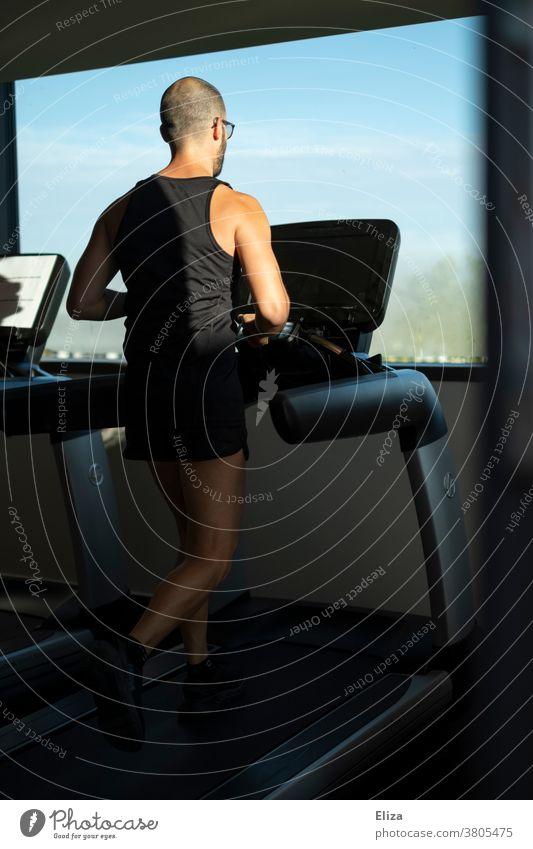 Mann trainiert auf einem Laufband mit Fensterblick im Fitnessstudio laufen Sonnenschein Sport Training Bewegung joggen drinnen Gerät Jogger Läufer laufend
