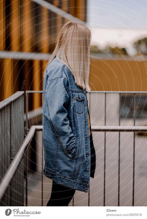 Junge blonde Frau im Profil im urbanen Raum jeansjacke lange haare Lifestyle Porträt hübsch schoen glücklich Erholung zufriedenheit lachen lächeln selbstbewusst