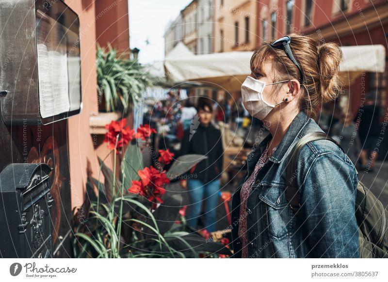 Junge Frau, die auf einer Straße in der Innenstadt steht und zur Seite schaut und die Gesichtsmaske trägt, um eine Virusinfektion zu vermeiden Pflege Kaukasier