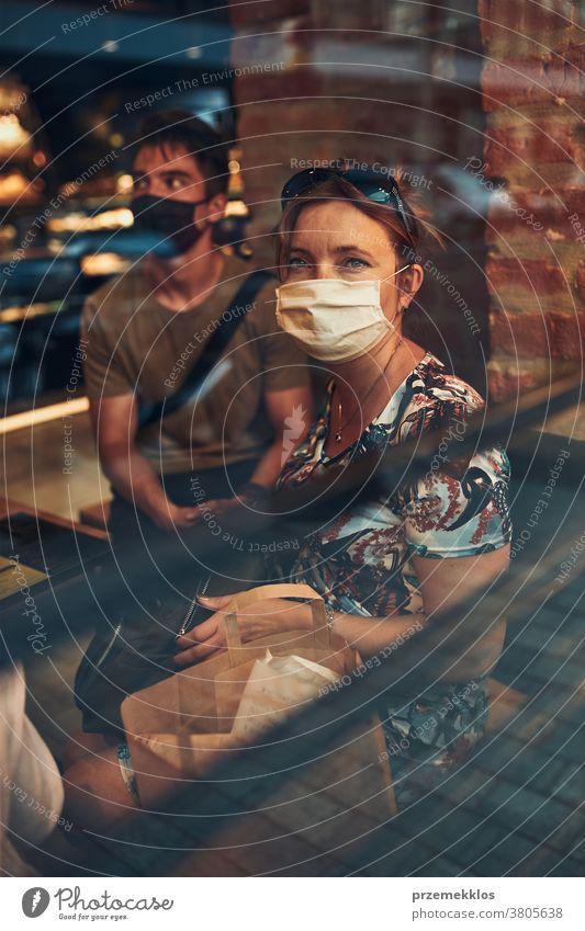 Familie sitzt im Café an der Ladenfront im Stadtzentrum und trägt die Gesichtsmaske, um eine Virusinfektion zu vermeiden Kaukasier Gespräch covid-19 Lifestyle