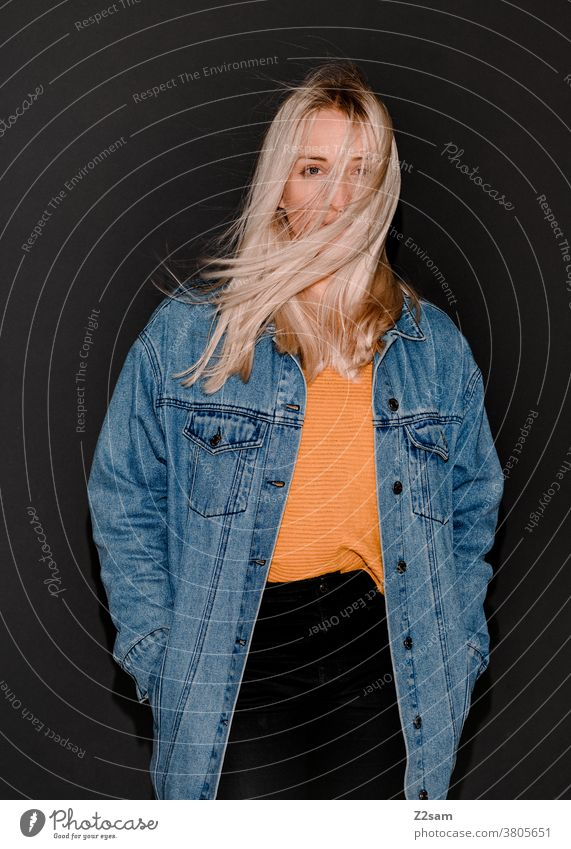 Mode-Portraits einer jungen Frau blond flashlook jeansjacke Paparazzi-Look trashig Modus Pullover Jacke lange haare hübsch Wind wehen Porträt schön Lifestyle