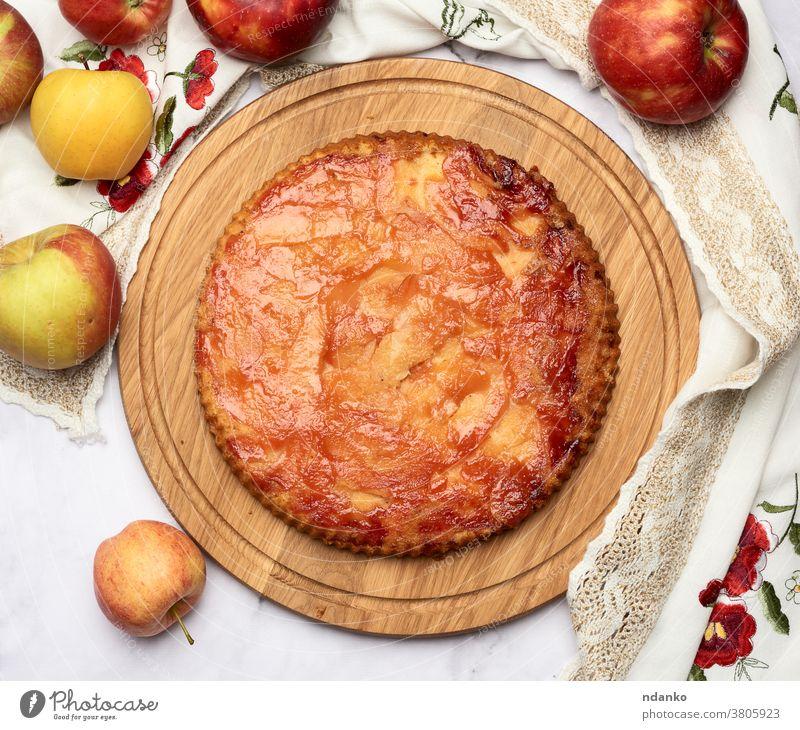 gebackener runder Apfelkuchen auf Holzbrettern und frische Äpfel Pasteten oben Kuchen Gebäck Dessert selbstgemacht Lebensmittel Amerikaner lecker Erntedankfest