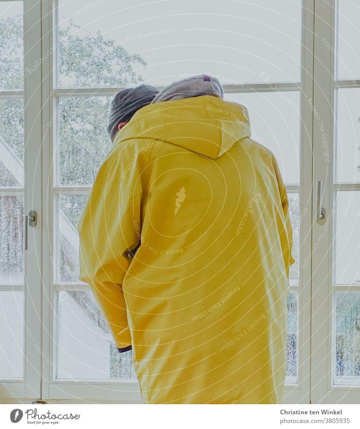 Mann steht bei Regenwetter am Fenster und zieht einen Friesennerz an | gefangen in Plastik Regenjacke Regenmantel schlechtes Wetter Schietwetter gelb