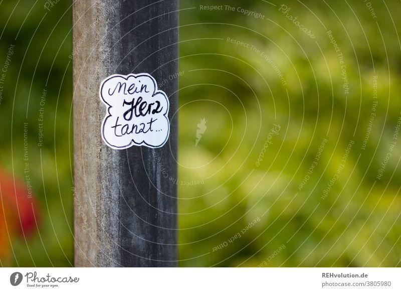 Aufkleber mit Spruch - mein Herz tanzt Idee kleben Text worte Laternenpfahl streetart Sticker Buchstaben Typographie Worte Kommunikation Hintergrund neutral