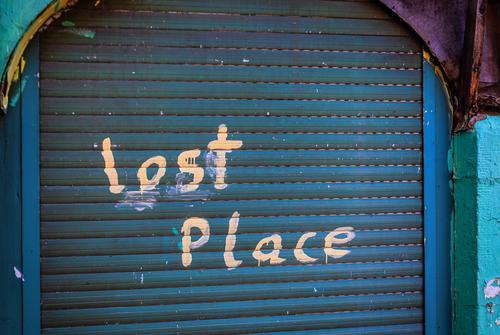 """Geschlossener Eingang mit Rolladen in blau, mit Handschrift """"lost Place"""" Lost Lost place verlassen geschlossen Wirtschaftskrise außer betrieb alt grün kaputt"""