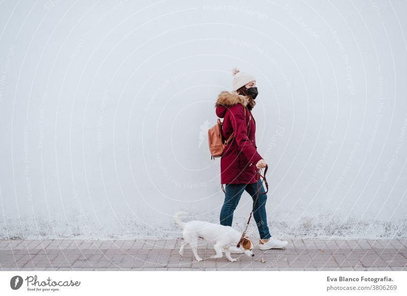 Frau mit Schutzmaske, die mit ihrem liebenswerten Hund Jack Russell durch die Stadt spaziert. Lebensstil im Freien Erwachsener allergisch Herbst Hintergrund
