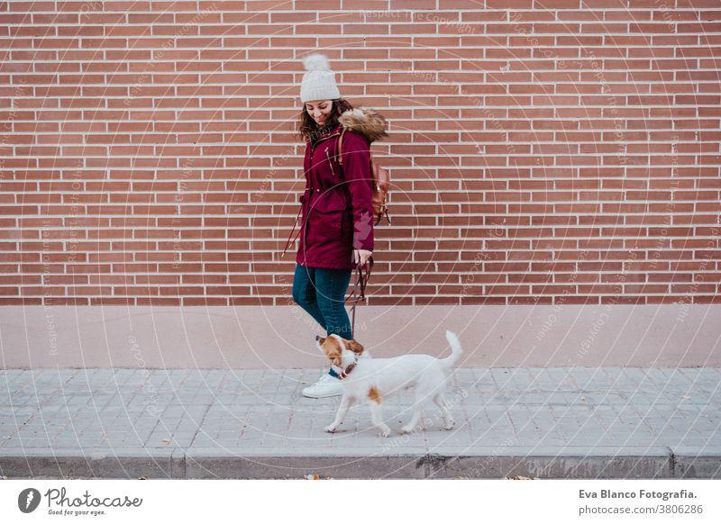 Frau in der Stadt beim Spaziergang mit ihrem entzückenden Jack-Russell-Hund. Lebensstil im Freien bezaubernd Herbst Backsteinwand Bulldogge Freizeitkleidung