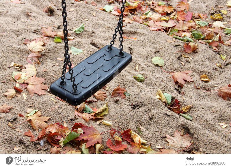 Herbststimmung auf dem Spielplatz - Schaukel hängt über regennassem Sandboden, der mit Herbstblättern bedeckt ist Schatten Blätter Ahornblatt Herbstfärbung