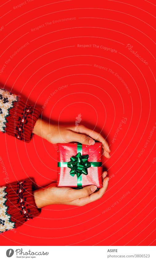 Frauenhände mit einem Winterpullover, der ein Weihnachtsgeschenk auf rotem Hintergrund hält. Weihnachten Geschenk Kasten präsentieren Hände Geben Entgegennahme