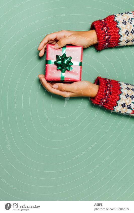 Frauenhände mit einem Winterpullover, der ein Weihnachtsgeschenk auf grünem Hintergrund hält. Weihnachten Geschenk Kasten präsentieren Hände Geben Entgegennahme