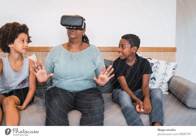 Großmutter und Enkelkinder spielen zusammen mit VR-Brillen. Großeltern Realität virtuell Zusammensein Simulation modern Gerät Konzept Simulator
