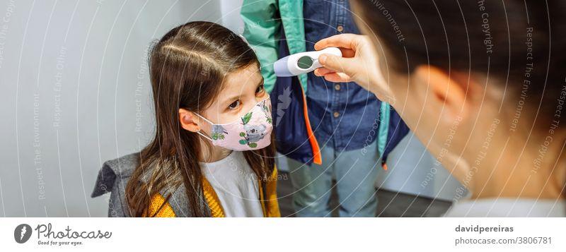 Mutter kontrolliert die Temperatur ihrer Tochter vor dem Schulbesuch berührungsloses Thermometer Überprüfung Gesichtsmaske Coronavirus Draufsicht Schutzmaske