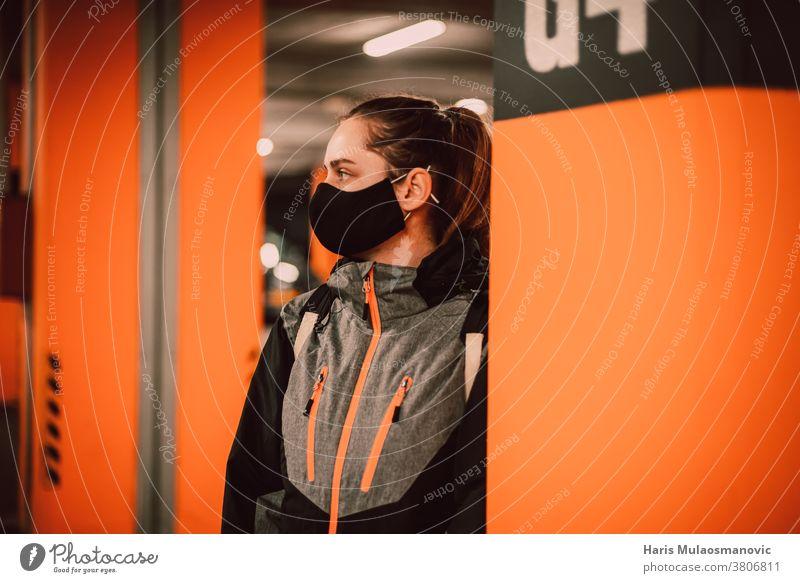 Frau mit Maske in der Garage an der orangefarbenen Wand Erwachsener attraktiv schön Schönheit schwarz lässig Sammlung cool Coronado-Brücke Coronavirus covid-19