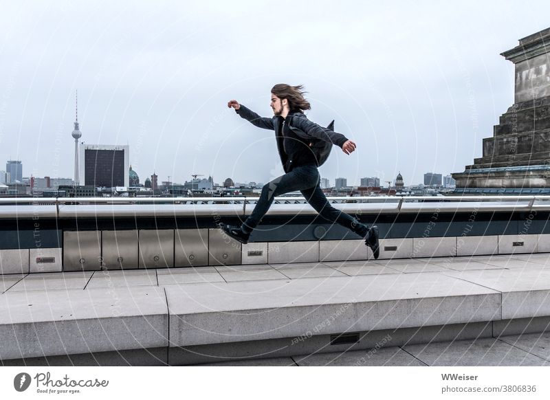 Mit großen Schritten springt oder schwebt der dynamische junge Mann über Berlin Panorama Reichstag Bundestag Kuppel Dach oben hoch Jugendlicher beschwingt