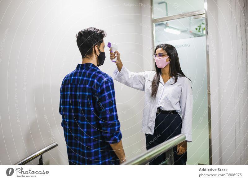 Frau misst Temperatur des fröhlichen Partners mit elektronischem Thermometer Männer messen heiter Kollege trendy hell benutzend Gerät modern digital Anzeige
