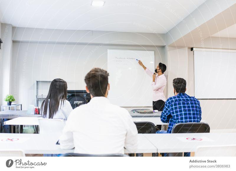 Anonymer Manager unterrichtet Kollegen in der Nähe der Markertafel im Klassenzimmer erklären Projekt Mitarbeiterin lehren zeigen Markierung Holzplatte