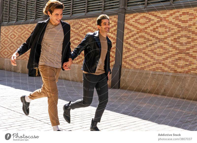 Glückliche stilvolle homosexuelle männliches Paar läuft auf Stadt Bürgersteig schwul laufen Händchenhalten Partnerschaft Liebe stylisch Bekleidung Straßenbelag
