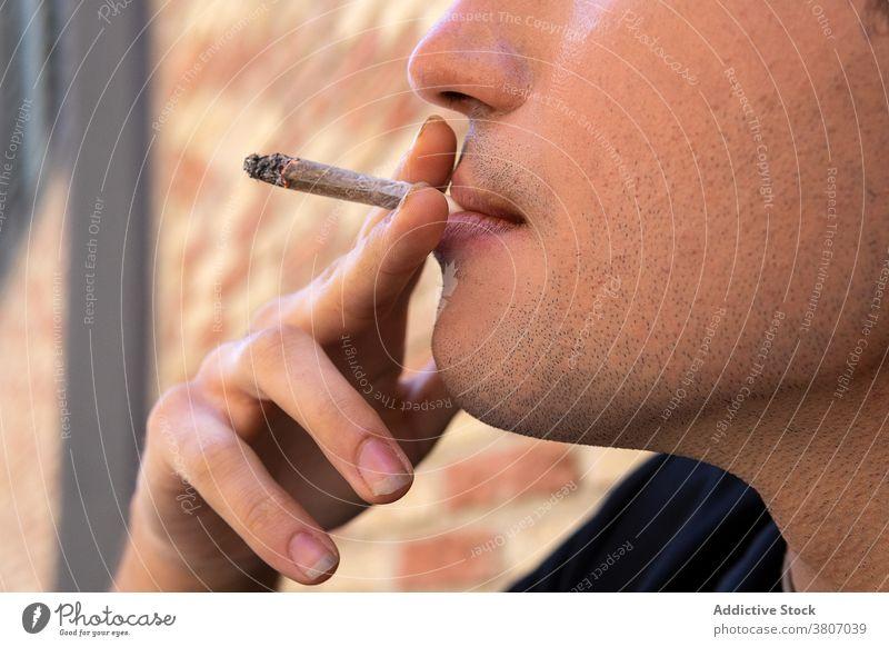 Anonyme stilvolle fokussierte Mann raucht Zigarette in der Nähe von Backsteinmauer Rauch stylisch Bekleidung Fokus Starrer Blick Backsteinwand Straßenbelag