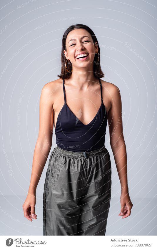 Fröhliche junge Frau in engem schwarzen Top im Studio expressiv Anmut Vorschein Stil Outfit cool traumhaft charmant Zahnfarbenes Lächeln Freude aufgeregt Figur