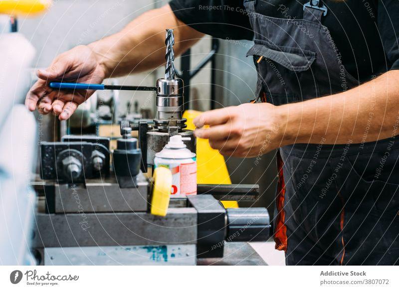 Crop gesichtslosen Mechaniker arbeiten mit Bohrmaschine in der Fabrik Mann Arbeit bohren Maschine Hobelbank Werkzeug Gerät Herstellung Arbeiter Instrument