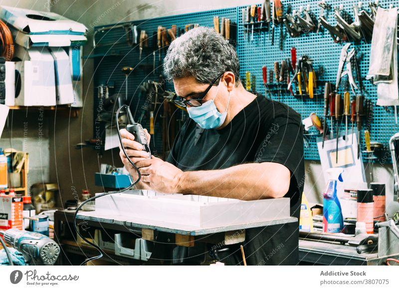 Professioneller Handwerker beim Maskenlöten von Details in der Werkstatt Mann Kunsthandwerker Fokus Arbeit Arbeitsplatz Beruf Kleinunternehmen Heimwerker