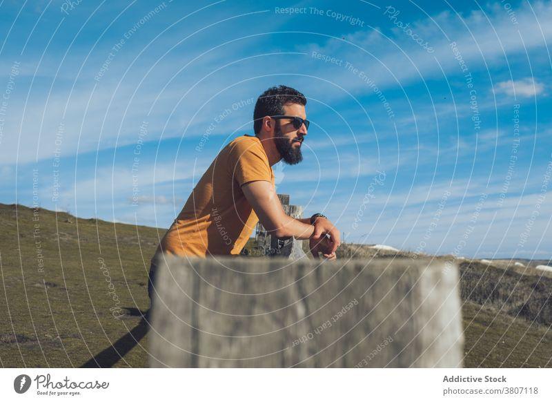 Selbstbewusster junger männlicher Reisender, der auf einem grasbewachsenen Hügel ruht Mann sich[Akk] entspannen bewundern Natur selbstbewusst Zaun Fernweh