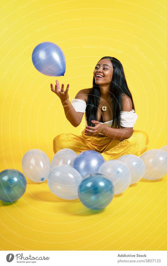 Fröhliche junge afroamerikanische Frau spielt mit Luftballons im Studio spielen Glück heiter Freude Stil Model Lächeln spielerisch positiv Optimist ethnisch