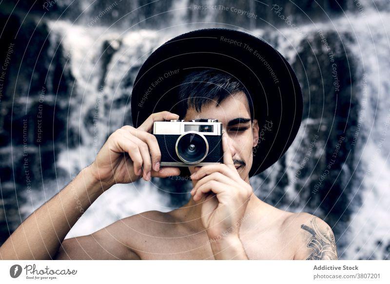 Stilvoller Mann nimmt Foto auf Vintage-Kamera altehrwürdig Fotoapparat Reisender fotografieren retro altmodisch Wasser Natur Wasserfall männlich Urlaub Hut