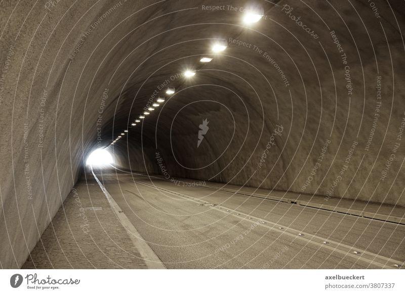 leerer beleuchteter Autotunnel Tunnel Straße Straßenverkehr Licht am Ende des Tunnels Unterführung Verkehr Transport reisen Zement Textfreiraum Hintergrund hell