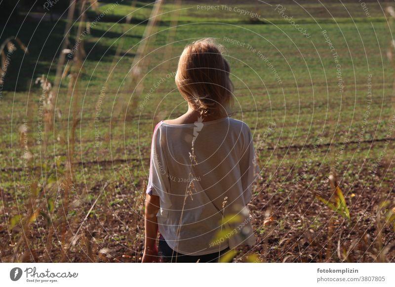 Mädchen schaut auf einen frisch grünen Acker Frühjahr Wachstum warten Ackerboden Rückenansicht Feld Landschaft schauen Ackerbau Landwirtschaft Frühling