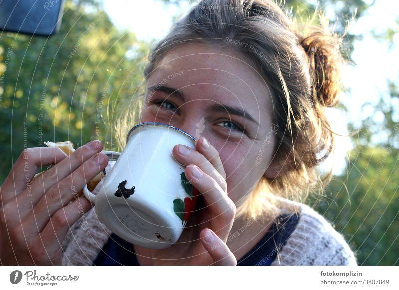 junge Frau im Grünen trinkt lächelnd aus einem Emaille-Becher trinken Emailletasse Tasse Frühstück Camping Heißgetränk Kaffee Getränk Kaffeepause Kaffeetasse