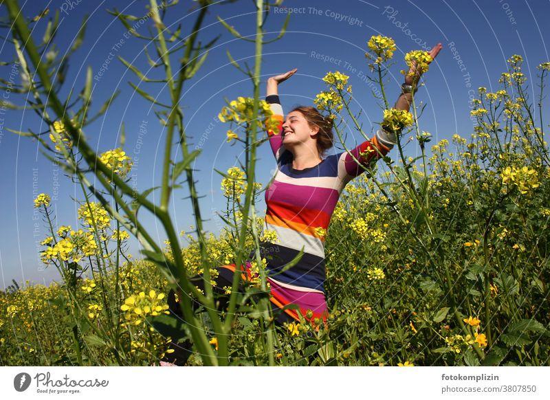 junge Frau springt mit erhobenen Armen in einem Rapsfeld Feld Optimismus Selbstvertrauen Lebensfreude Glück freuen sich freuen jauchzen strecken Lebenslust