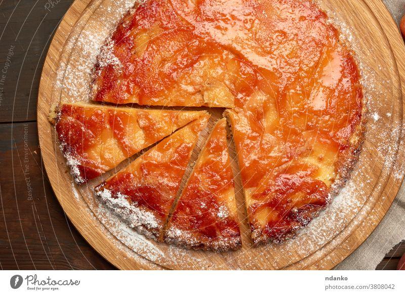 gebackener runder Apfelkuchen auf Holzbrett a oben Amerikaner Pasteten süß Tisch Torte geschmackvoll Erntedankfest Top traditionell ganz hölzern Herbst braun
