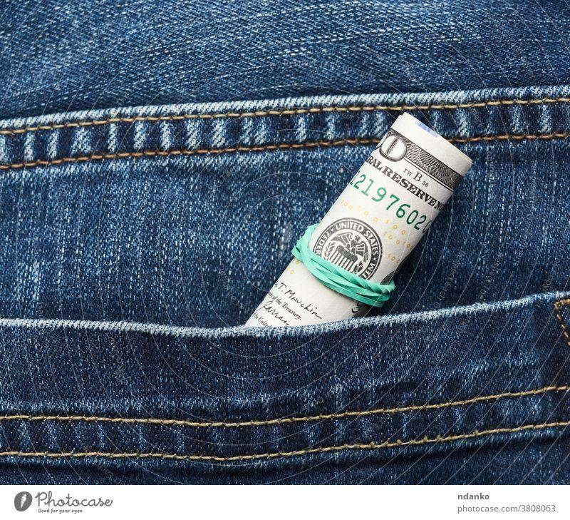 Hundert-Dollar-Scheine aus Papier zusammengerollt und mit grünem Gummiband festgezogen Gewebe Finanzen finanziell Franklin hundert Investition Jeanshose Geld