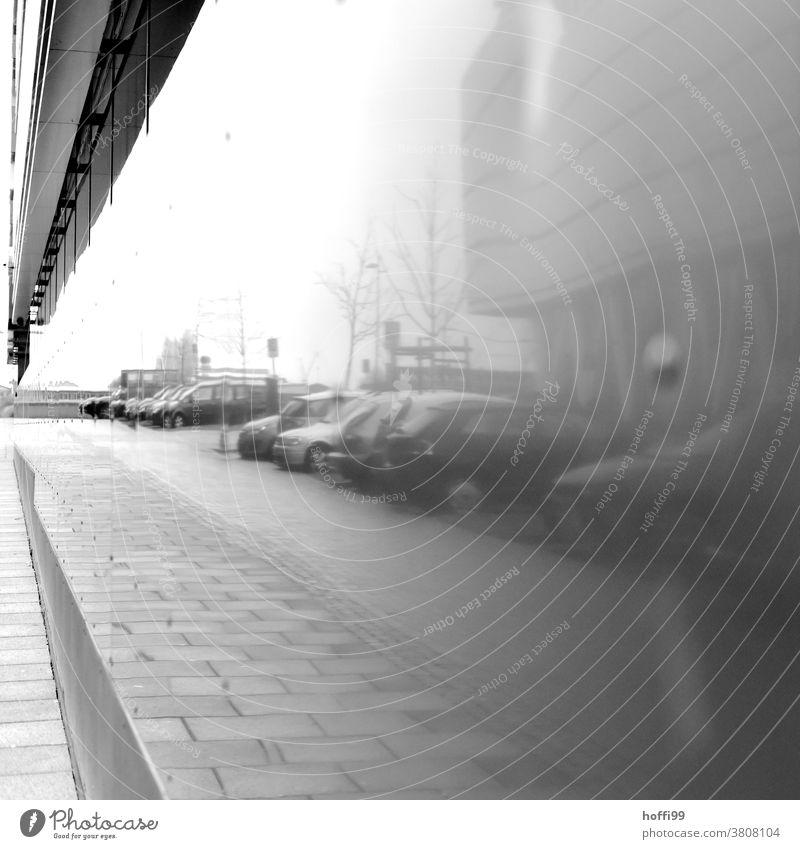 geparkte Autos am Straßenrand, reflektiert von einer Bürofassade Reflektion Reflexion & Spiegelung Reihe Herbst Herbststimmung Nebel herbstnebel Nebelschleier