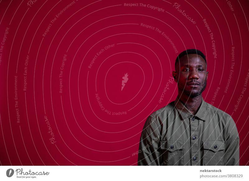 Junger schwarzer Mann posiert im Studio auf isoliertem roten Hintergrund Textfreiraum Porträt afrikanische ethnische Zugehörigkeit eine Person männlich