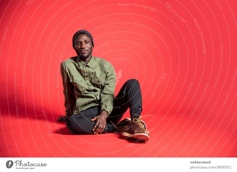 Junger schwarzer Mann posiert auf dem Studioboden sitzend Inhalt Pose afrikanische ethnische Zugehörigkeit eine Person männlich Nur ein Mann 20-30 Jahre alt